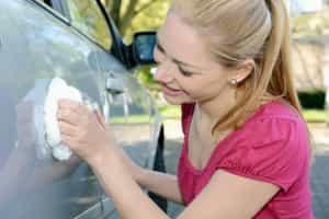 Frau poliert Autolack mit Politur